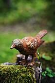 Rusty metal bird figurine on mossy tree stump
