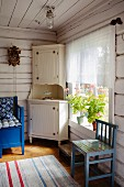 Corner of rustic living room in wooden house - white corner cupboard next to window and blue kitchen chair