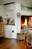 Corner of rustic interior with blazing fire in open fireplace