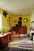 Rustic interior with yellow-painted walls, various rugs striped in different colours, rattan armchair and sideboard