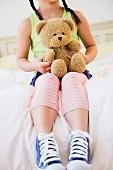 Girl sitting on bed holding teddy bear