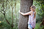 Teenage girl hugging tree in woods