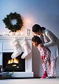 Mother and daughter next to festively decorated fireplace