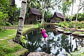 Girl swinging on rope in garden (Ubud, Bali, Indonesia)