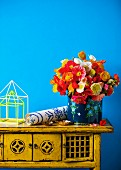 Colourful bouquet and roll of wallpaper on vintage cabinet against blue wall