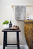 Rattan laundry basket next to antique shoe lasts and toiletries on vintage stool