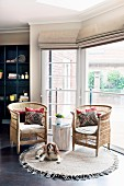 Seating area in window bay with wicker armchairs and dog on round, fringed rug