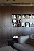 Books and pictures on shelves of dark living room cupboards; grey sofa in foreground