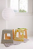 Laminated wood stools covered in patterned wallpaper below round, white paper lampshade