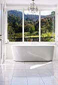 Chandelier and free-standing designer bathtub in sunny bathroom with view over woodland landscape