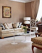 Classic interior in shades of beige with graphic pattern on upholstered furniture and Italian, fifties-style tulip tables