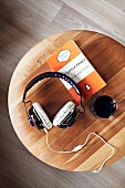 Headphones, beaker and book on wooden stool (top view)