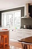 Moderne weisse Einbauküche mit dunkel getönter Rückwand