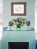Open fireplace painted pale grey as partition; bouquet and ethnic masks on mantelpiece