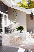 Delicate metal chairs and table on stone floor of sunny terrace adjoining wooden house
