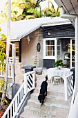 Dog on steps leading to furnished terrace of wooden house