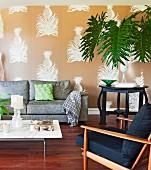 Wohnzimmer mit 50er Jahre Sessel, modernem Sofa und goldfarbener Tapete mit Ananas-Motiven