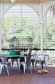 Birdcage on table and retro-style metal chairs in garden pavilion with slatted screens