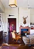 Living room with rustic ambiance; 50s-style armchairs in front of open fireplace below hunting trophy