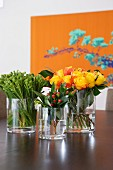 Bouquets in glass vases on table; large floral artwork in background