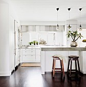 Wooden barstools at counter with concrete worksurface below simple pendant lamps in open-plan kitchen