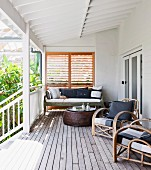 Rattan armchairs and coffee table on roofed wooden veranda adjoining house