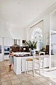 Child next to kitchen counter and barstools in open kitchen with tiled floor in Mediterranean ambiance