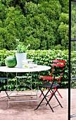 Blick durch offene Terrassentür auf farbige Klappstühle und Gartentisch vor berankter Efeu Mauer und Waldrand