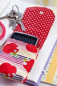 Open mobile phone pouch with pattern of apples on stack of books