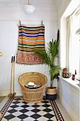 Ethnic wall hanging above wicker armchair and potted palm tree on diagonal chequered floor