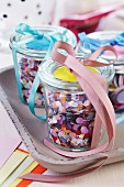 Colourful confetti in jars decorated with ribbons
