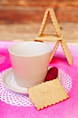 Biscuit next to white cup and saucer on place mat sprayed hot pink through doily stencils
