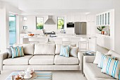 Ecru sofa and ottoman in front of white kitchen area with counter and bar stools