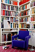 Royal blue armchair and standard lamp in front of bookcases