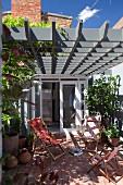 Deckchairs on sunny terrace below grey wooden lattice pergola adjoining house with open door