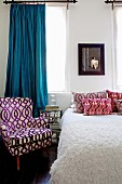 Armchair and scatter cushions with covers in various retro patterns and pale bedspread on bed