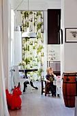 Kleines Kind auf Kinderstuhl in Küche, seitlich Retro-Stuhl an rundem Tisch, im Hintergrund raumhoher, gemusterter Vorhang