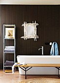 Bathroom display - simple wooden bench, bathtub, metal shelves and mirror framed with white sticks on dark brown wooden wall
