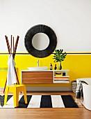 Gelber Hocker auf schwarz-weiss gestreiftem Teppichläufer, an gelber Wand aufgehängter Waschtisch unter rundem Spiegel mit dunklem Rahmen