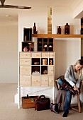 Woman sitting on chair in hall next to chest of drawers, display case and floating shelf