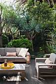 Grey-upholstered outdoor furniture and coffee table on wooden terrace with yuccas in mature garden in background