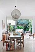 Vintage dining table and bamboo chairs below pendant lamps with spherical mesh lampshades and view of outdoor furniture and garden through open terrace doors