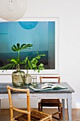 Blue reflective artwork behind vintage table with metal top, bamboo chairs and green leaves arranged in demijohns