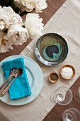 Cutlery on blue napkin on plate next to bowl with peacock-heather motif and small wooden bowls on pale linen runner