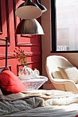 Red pillow on bed, wire mesh side table and white armchair below window against wooden panelled wall painted light red