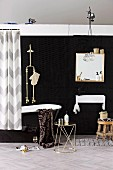 Black bathroom - metal side table, black glossy bathtub with shower head and mirror above sink against black wall
