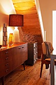 Lit retro table lamp on fifties sideboard below wood-clad underside of staircase and on rustic wooden floor