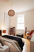 Double bed and wicker pendant lamp suspended from white wood-clad ceiling in simple bedroom with trunk and guitar next to retro armchair against wall