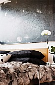 Stacked black pillows and fur blanket on bed below black painting on wall