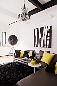 Dark grey leather corner couch on long-pile, black rug, chandelier and studio lamp in designer interior